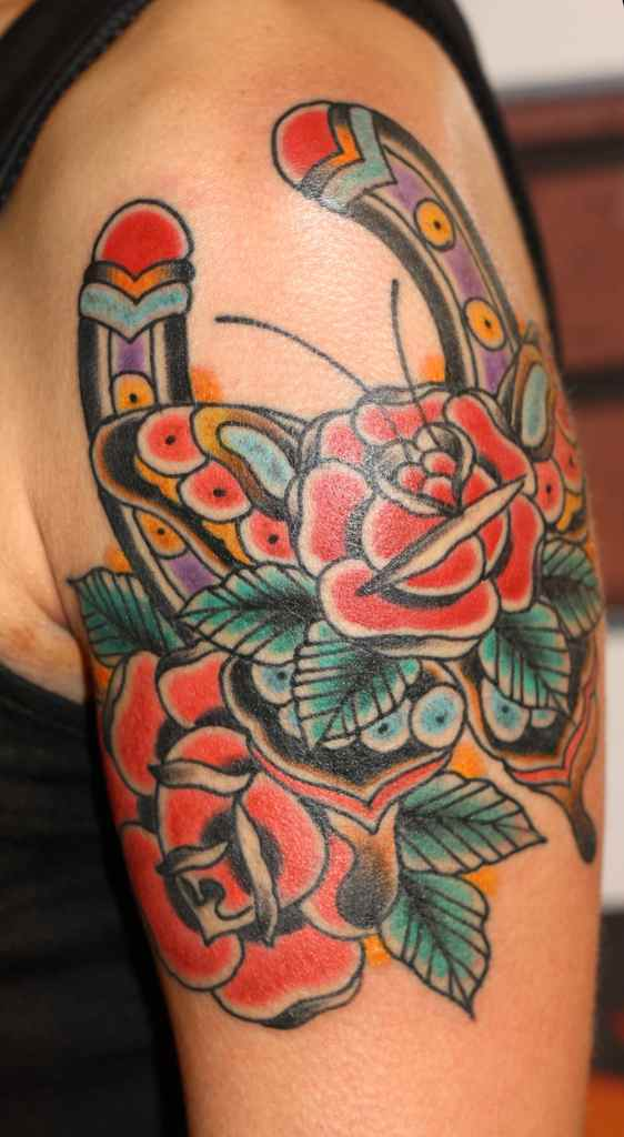 Red flowers and horse shoe tattoo
