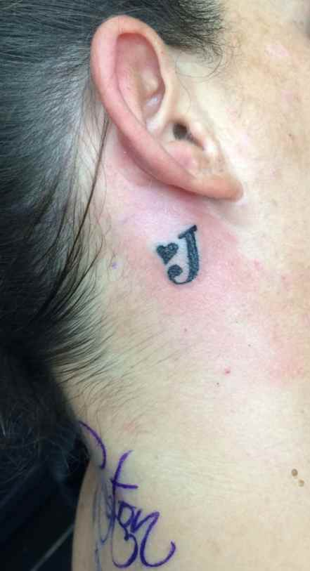 Tattoo lettering behind the ear